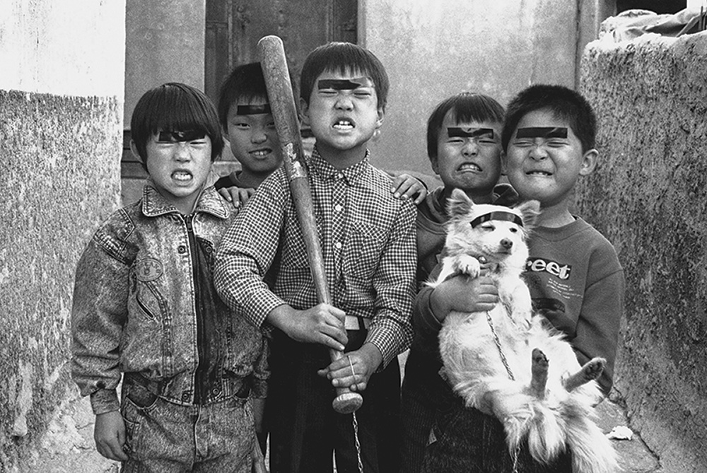 "A classic Kim-Ki-chan image, one of many he committed to film as he went about documenting the golmok, Seoul's back-alleys, where he identified as the formative space for Korean manners, mores, and the backbone of Korean identity itself. I am strongly of the opinion that one of the reasons Kim Ki-chan receives so much popular, positive historical attention relative to many other photographers active during the 60s and 70s is because his depiction and view of Korean development-era life seems to say, quite simply, ""Things were kind of tough at times, but overall, they weren't so bad and it gave our people character."" They weren't exactly ""good times,"" but they weren't all that bad, either."