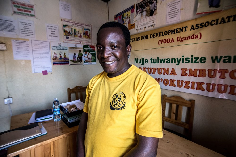 Noah Musoke sits in the VODA project office in Kasawo decorated with posters encouraging young people to feel welcome