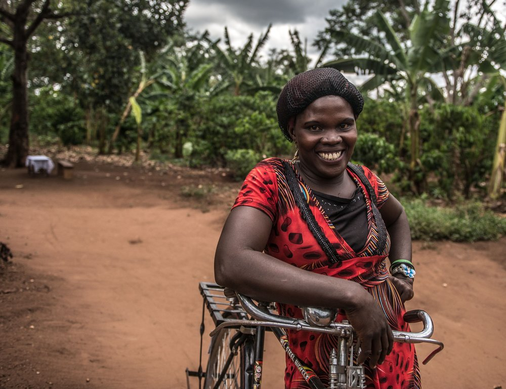 Christine, a VODA community volunteer, with the bike she uses to visit clients, outside her house near Kasawo, Uganda.