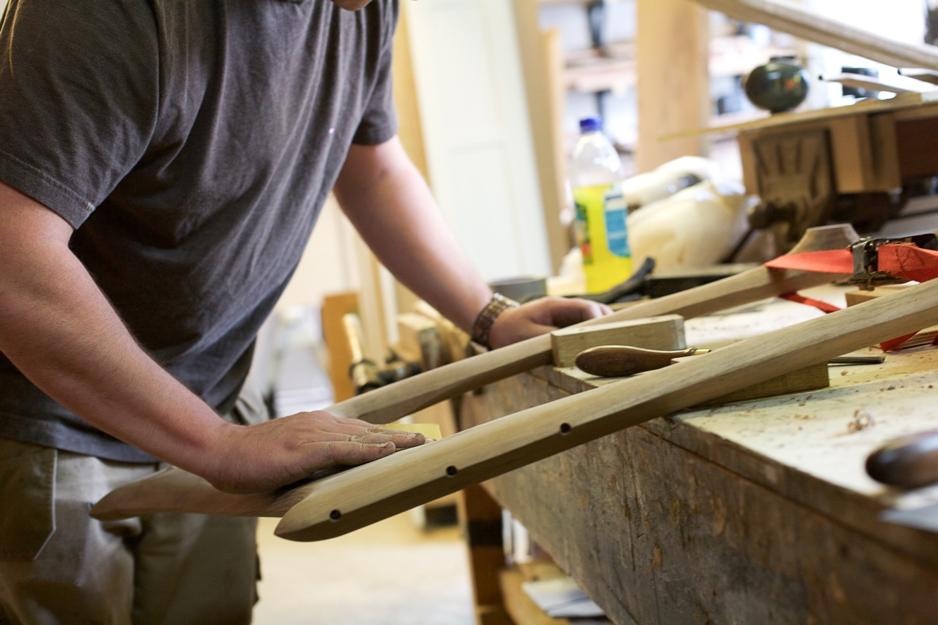 Man at Auspicious Furniture sanding wood