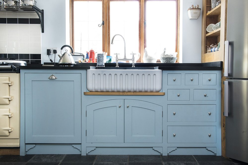 Blue kitchen cabinets with embedded Ribchester sink