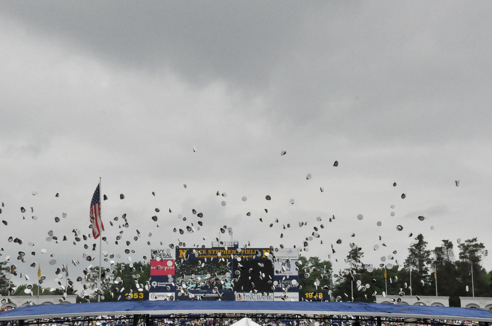 Midshipmen throw their covers after becoming officers following their graduation from the United States Naval Academy in Annapolis, Maryland.
