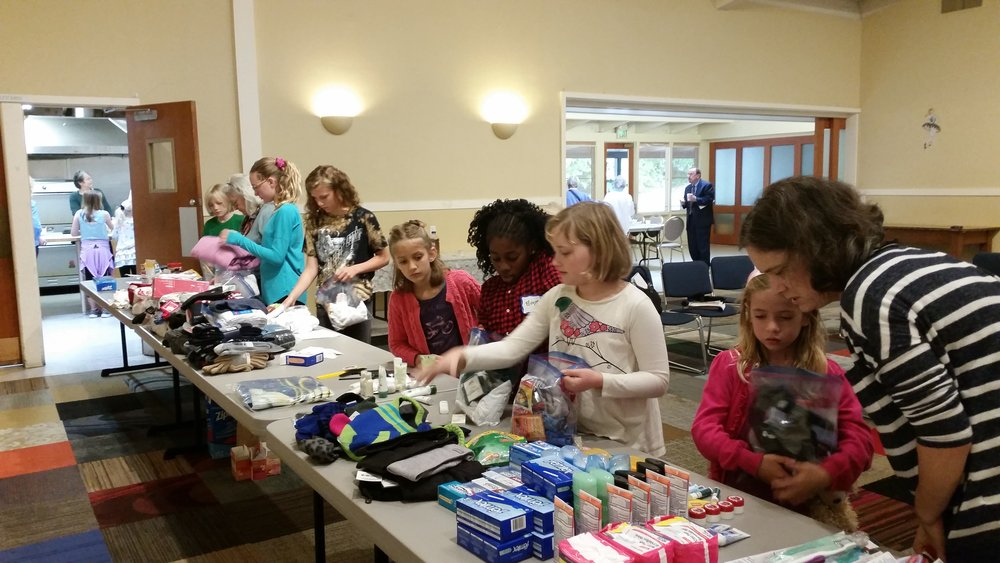 "Children and Youth helping pack ""Blessing Bags"" to hand out to people in need in our communities"