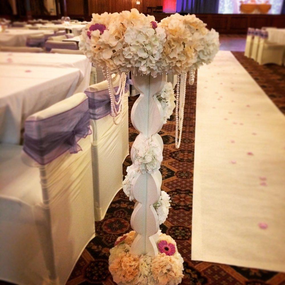 Neutral hydrangea floral walkway pillars with added hot pink geberas.
