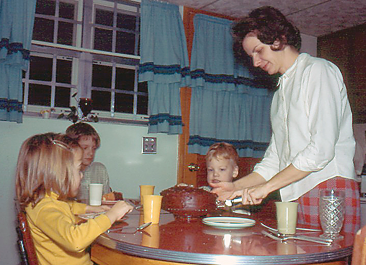 Diane cutting cake with all three children around the dinner table