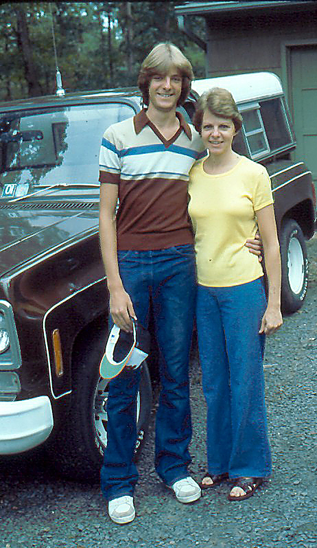Diane and her son Al stand in front of their old, brown pickup truck
