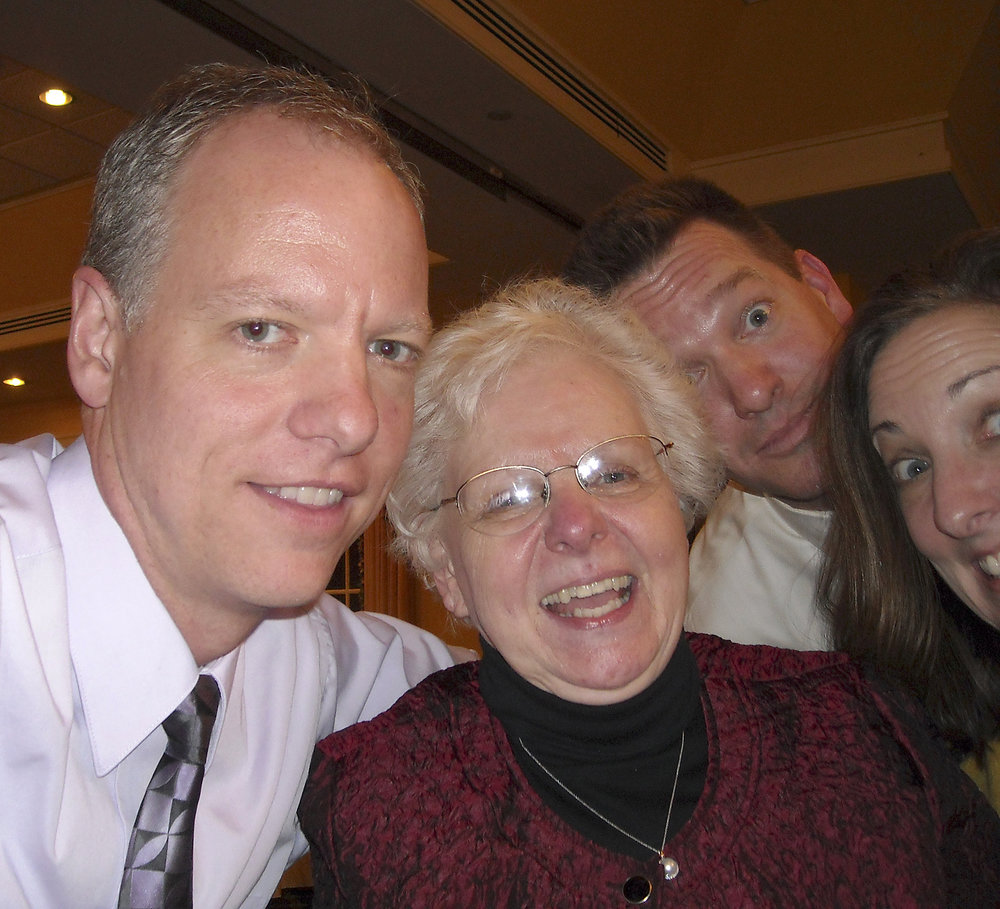 Diane and Chris' traditional selfie photo being photo-bombed by her daughter, Jackie, and son-in-law, George at Diane's 70th birthday party
