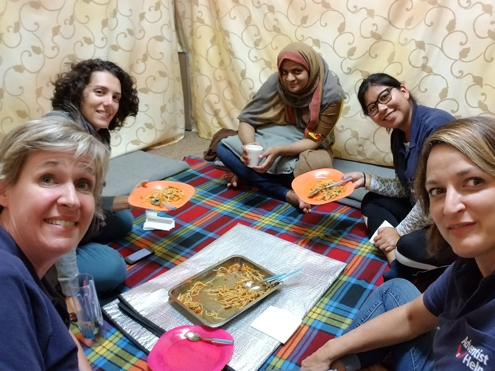 Karah Thompson (right) sharing a meal with a Pakistani refugee.