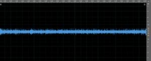 Original source audio waveform with low volume & loud ambient noise masking speech content.