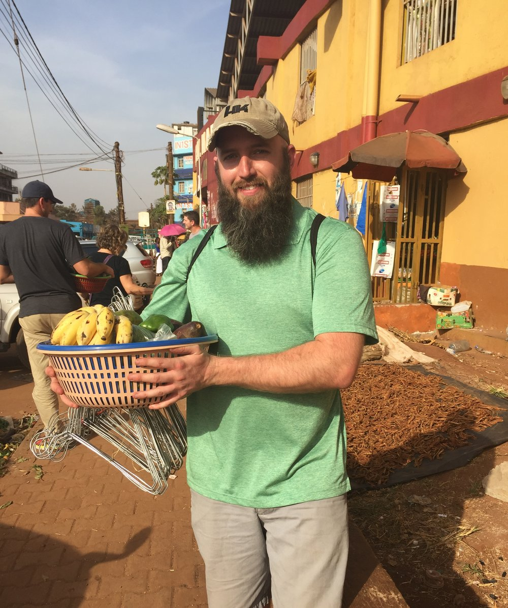 Gabriel standing with our basket of purchased goods, just outside of Central Market in Jinja-town.