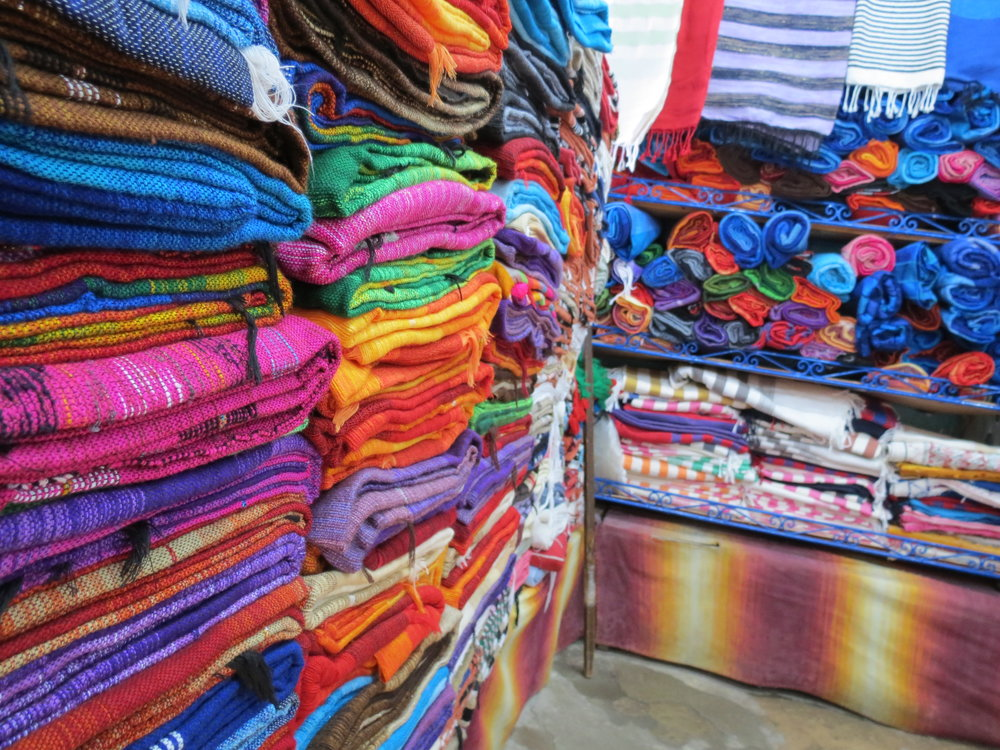 Artisan weavers craft colorful Moroccan blankets on looms in Chefchaouen.