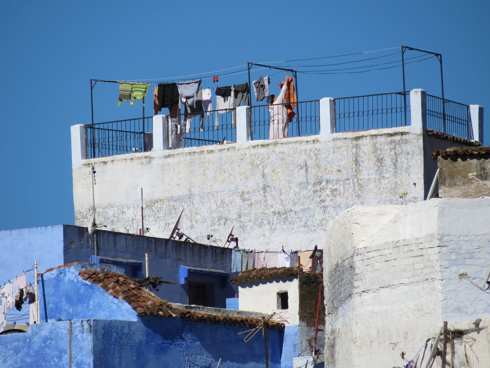 A woman hangs laundry to dry on her rooftop terrace in Chefchaouen, Morocco.