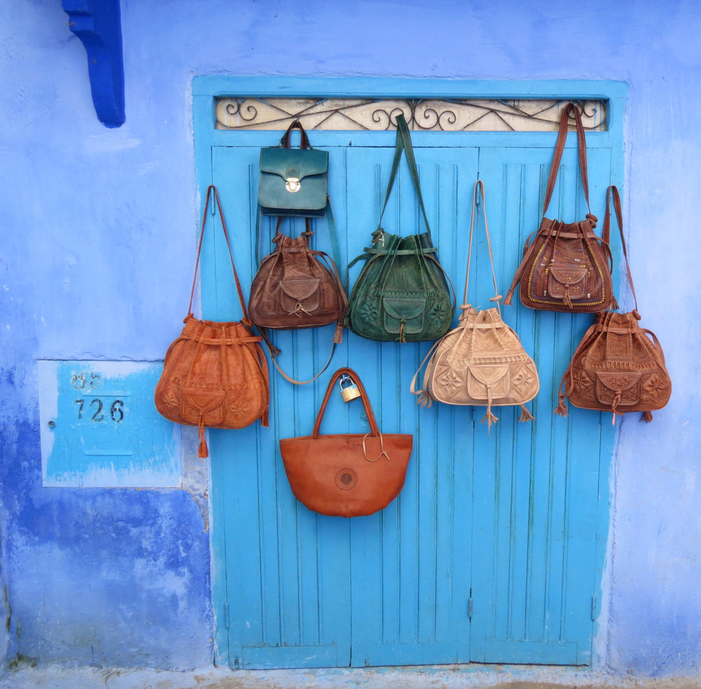 Handmade leather bags are showcased against blue-washed walls in Chefchaouen, Morocco.