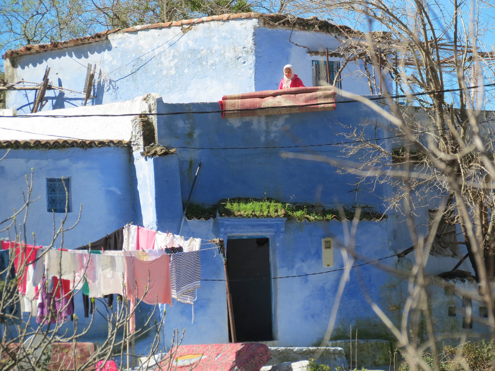 A Moroccan woman hangs laundry and beats rugs at her family's farm house in Chefchaouen.