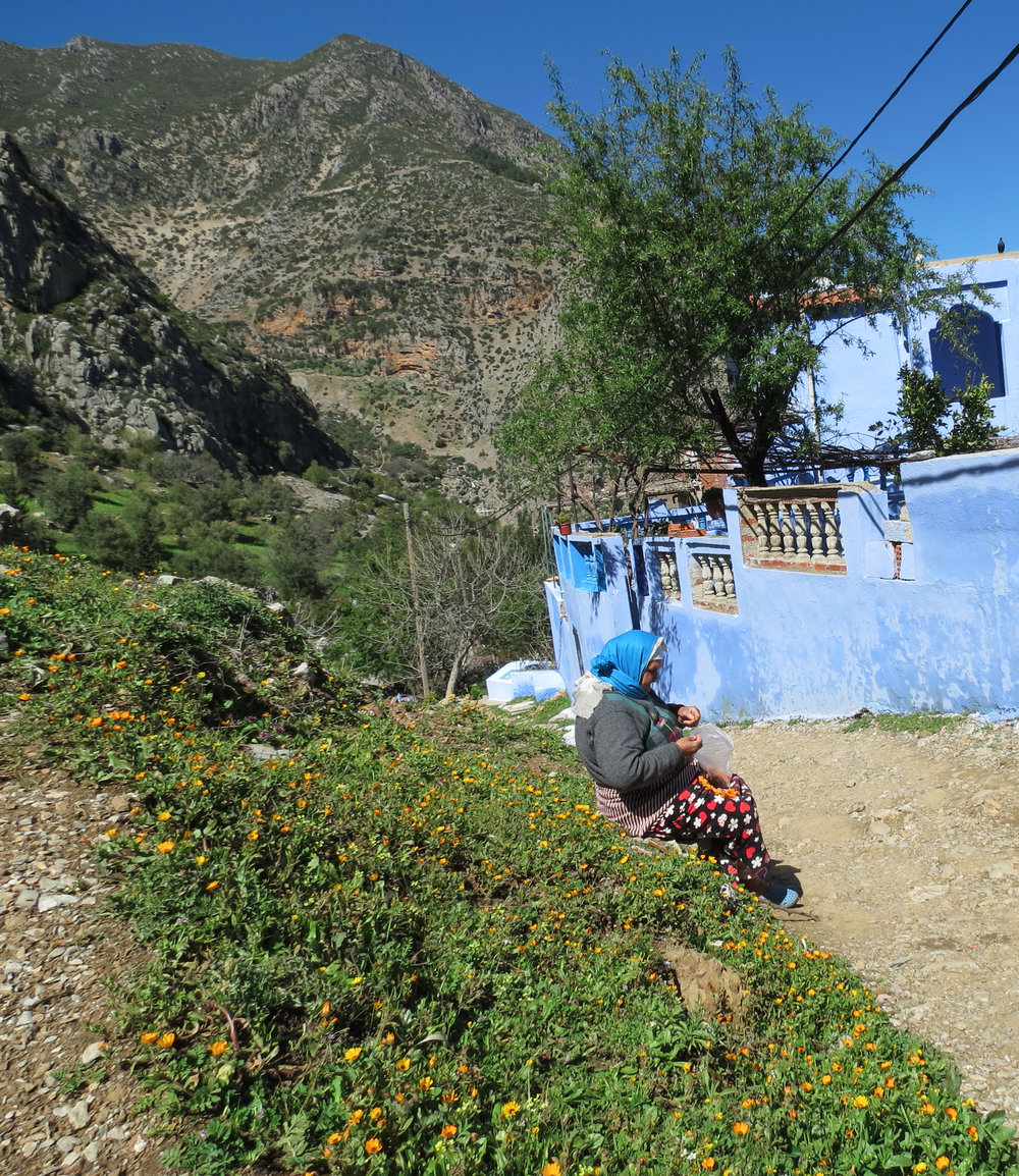 A woman sews flowers together into necklaces, just outside of Chefchaouen, Morocco.