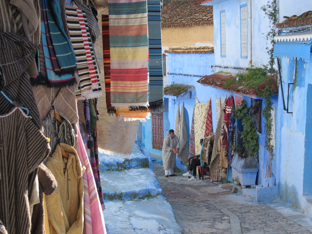 Moroccan artisans display their works along the blue-washed walls of Chefchaouen's traditional souk.