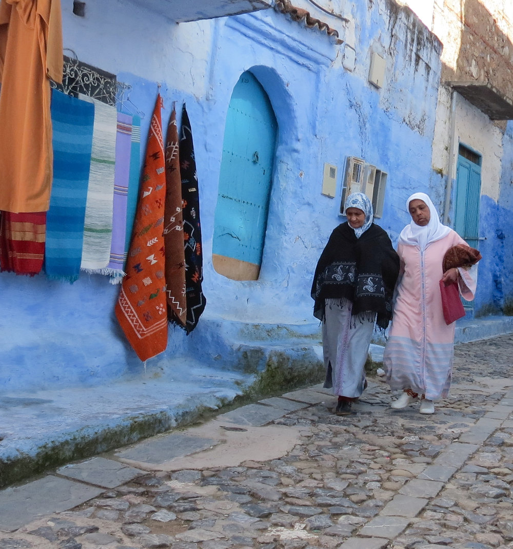 Two Moroccan women walk through the traditional souk of Chefchaouen, Morocco.