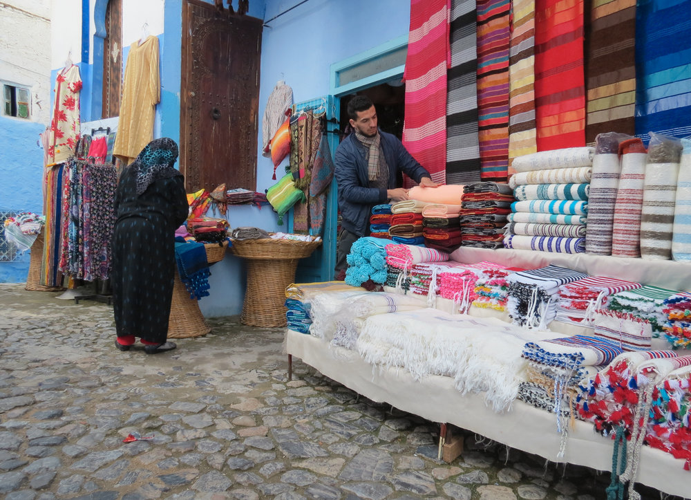 Shop in the medina, a traditional souk in Chefchaouen, Morocco, where you'll find clothes, home décor, and other handmade goods, crafted by local artisans.