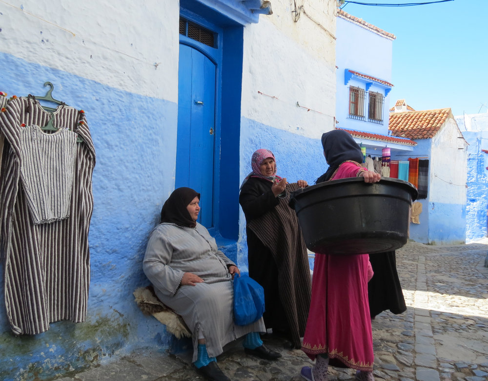 Moroccan women pause to greet each other and share the latest village gossip in Chefchaouen.