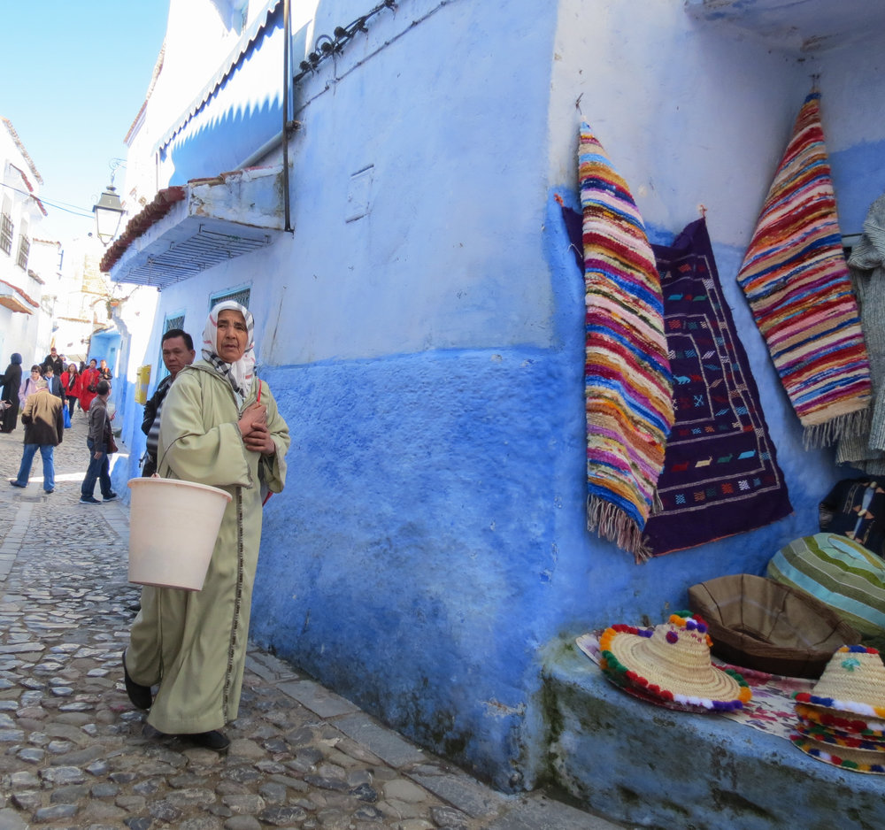 A Moroccan woman walks through Chefchaouen's medina, set in the small village in the Rif Mountains of Morocco.