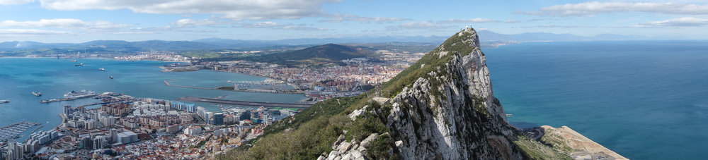 A panoramic view of the Rock of Gibraltar with surrounding Spanish coastline, Mediterranean waters, and entrance to the Atlantic.
