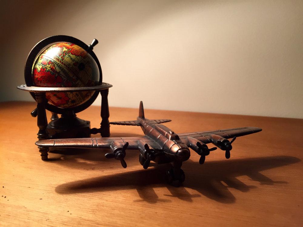 Airplane and globe travel graphic.