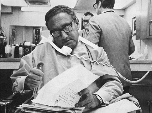 Henry Kissinger working while getting a haircut.