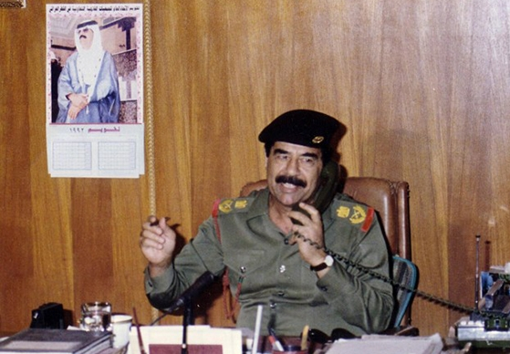 Saddam Hussein making orders from his office.