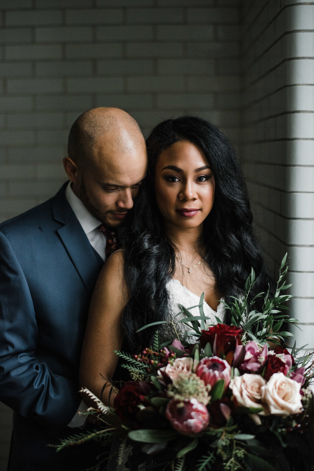 Wedding portrait of bride and groom with protea and roses. Des Moines, IA. Photographed by Austin Day.