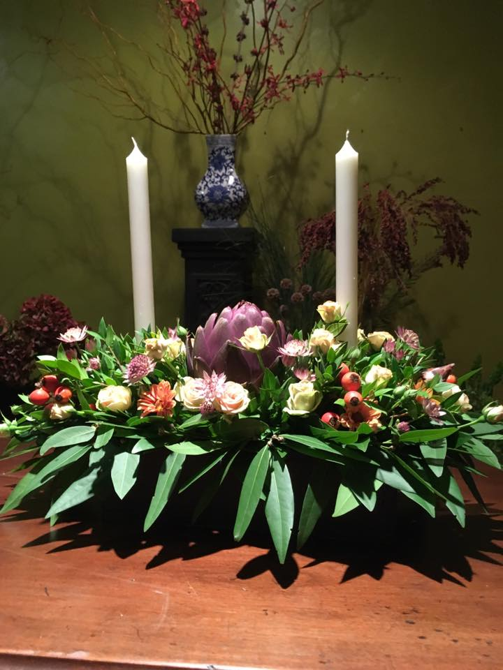 Thanksgiving centerpiece with flowers, leaves and pods.