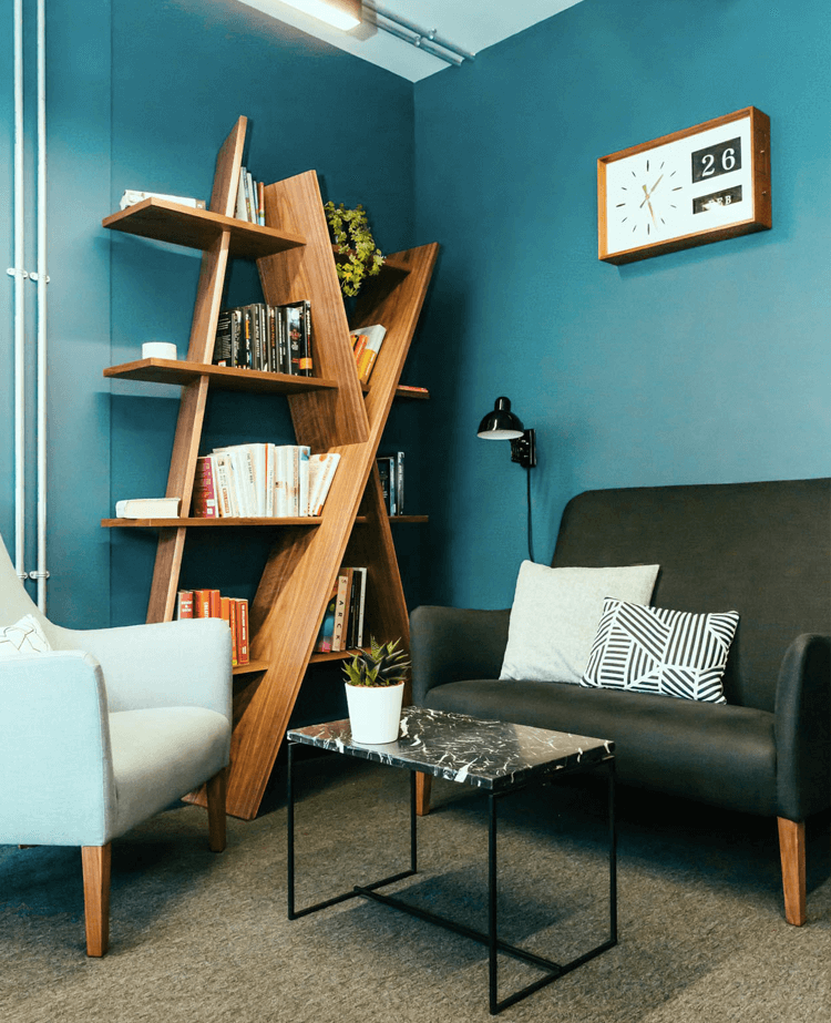Stylish office sofa and table with bookshelf and wall clock