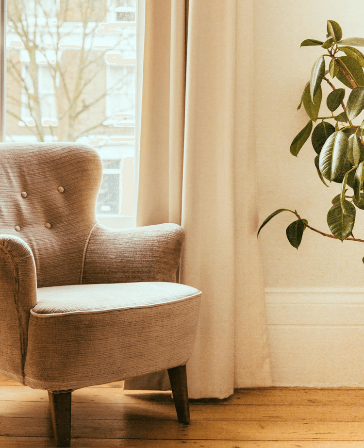 White arm chair by window