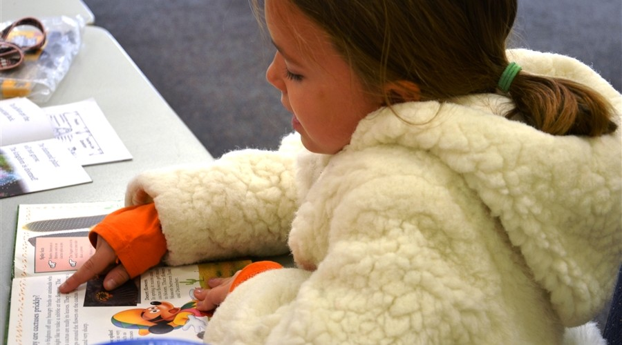 little-girl-reading-in-white-fuzzy-coat-900x500.jpg