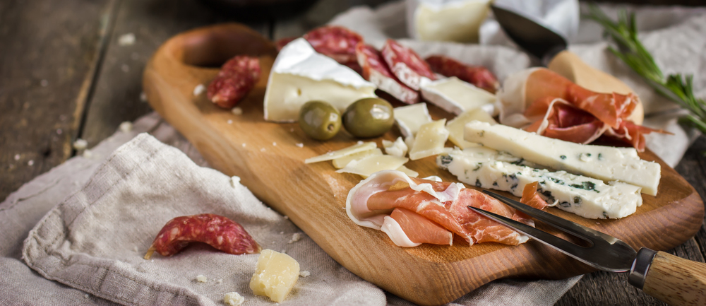 stock-photo-appetizers-various-types-of-cheese-salami-and-prosciutto-on-wooden-cutting-board-rustic-292123916 (1)_cropped.jpg