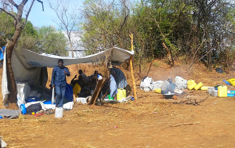 """New """"permanent homes"""" are erected for the South Sudanese refugees. Most are coming across the border with nothing but the clothes on their backs. These tarp tents are meant to protect them from all the elements: rain, wind, and soaring African heat."""