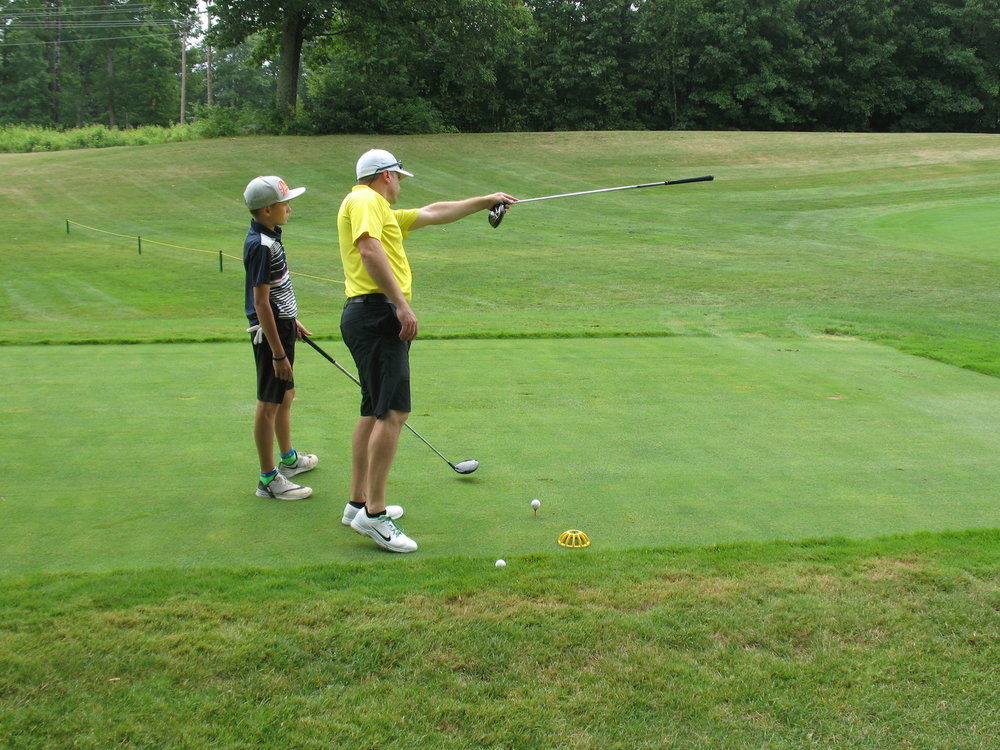 A young golfer gets some pointers from his dad
