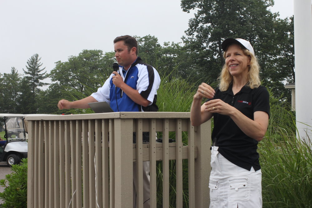 Krista Brown, ChildVoice staff member and golf tournament coordinator, interprets welcoming remarks from The Oaks' golf pro, Craig McLaughlin.