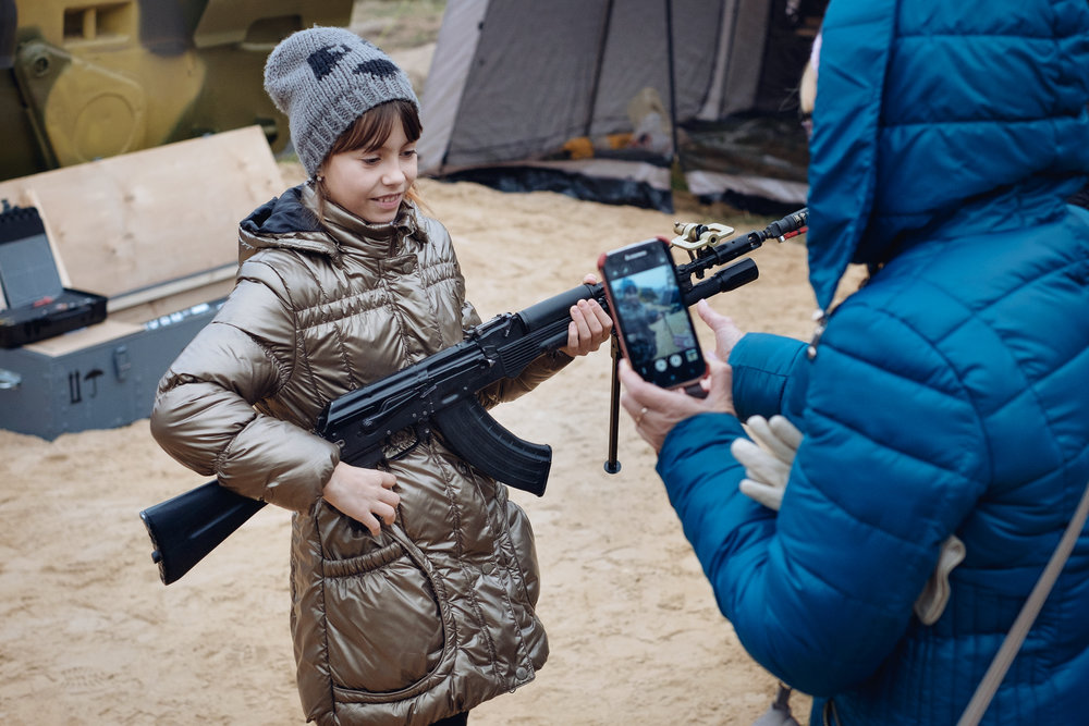 """A young girl is being photographed by her mother while holding a Russian Kalashnikov automatic rifle during the 19th homeland security exhibition """"INTERPOLITEX"""". Military base, Russia,2015."""