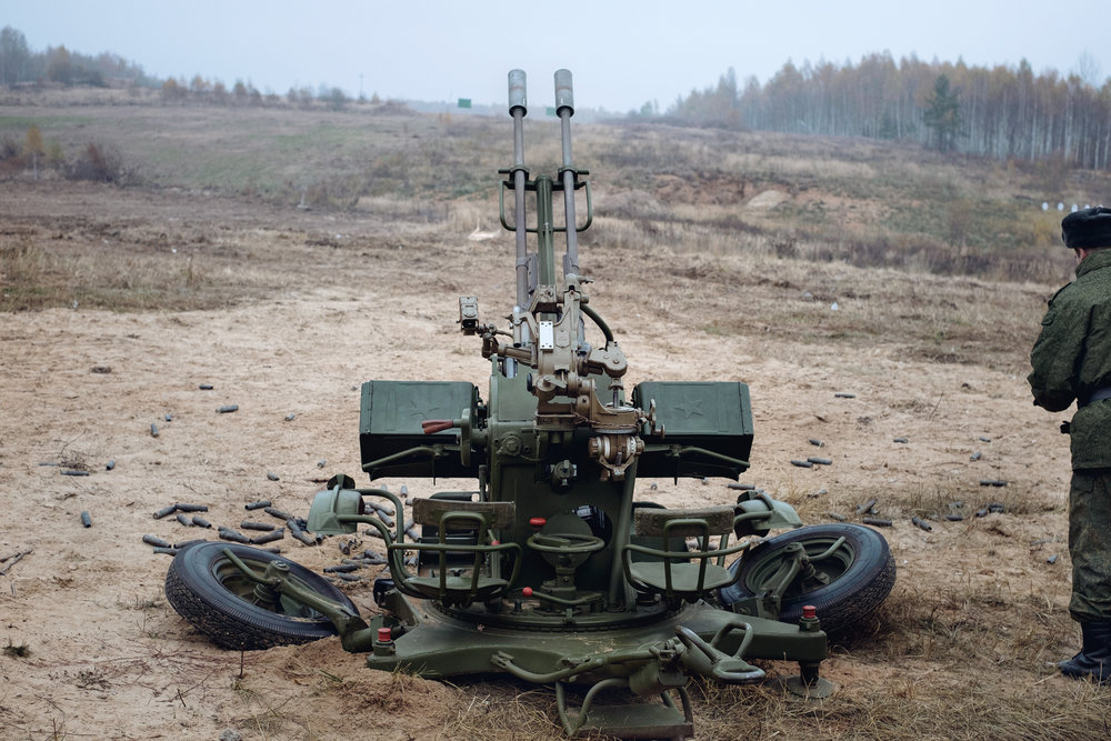 """Empty rounds lying around a Russian ZU-23 """"Sergey"""" anti-aircraft cannon after a live demonstration during the 19th homeland security exhibition """"INTERPOLITEX"""". Military base, Russia,2015."""