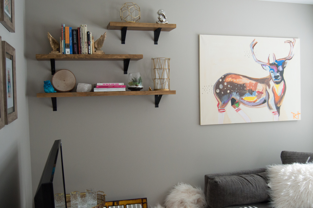Notice the balance of space between the couch, the ceiling, the bookshelf and the art in this image. All items are spaced appropriately and nothing is too far apart. Give it a try!