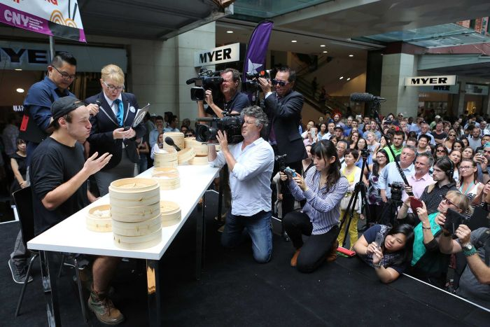 Isaac Harding going for gold at the Guinness World Record title for eating the most dumplings in two minutes at Pitt Street Mall, Sydney. ABC: Lisa Clarke