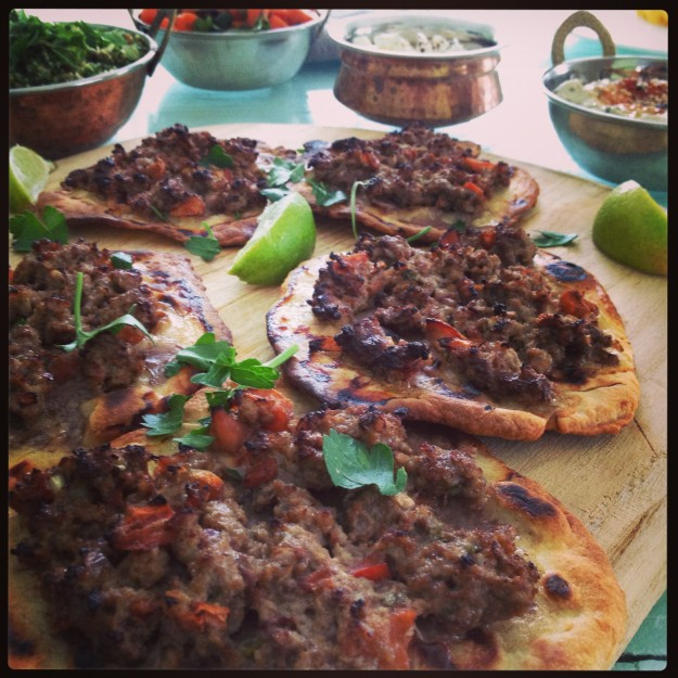 Middle Eastern pizza served with sides and wedges of lime.