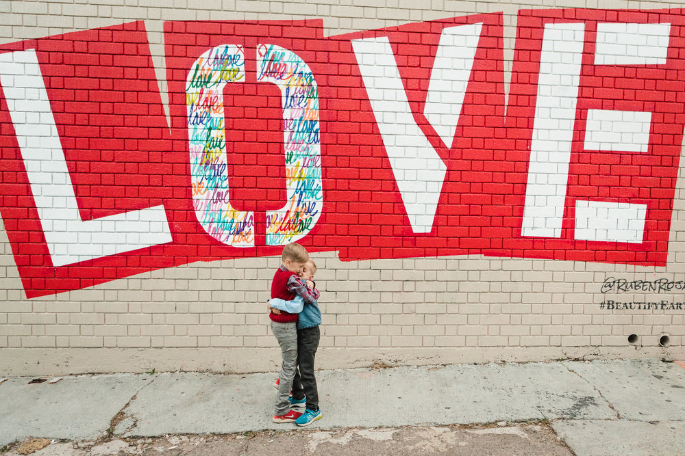 brothers hug at the love mural wall in san diego, california