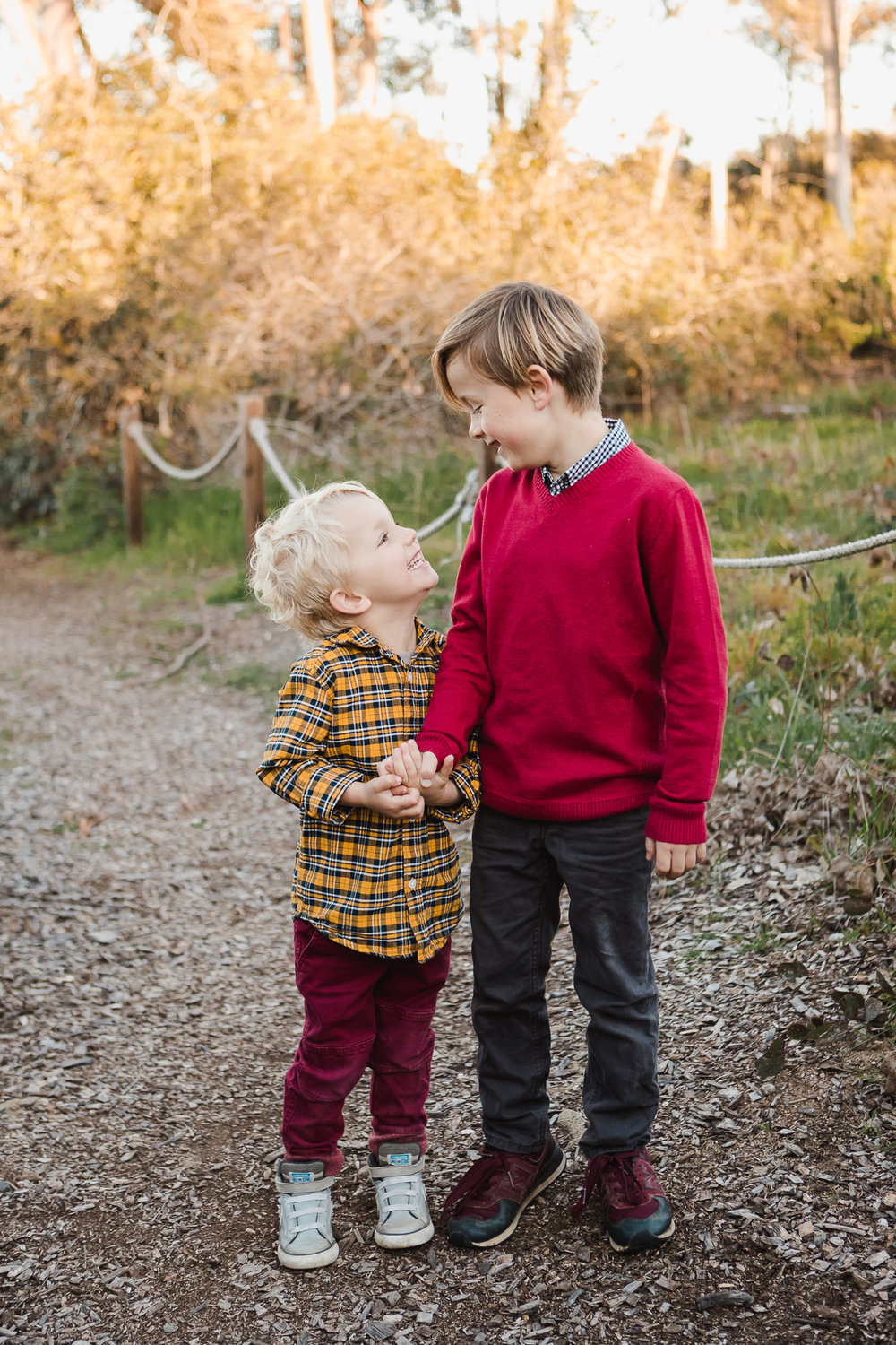 Little boys in brightly colored clothing holding hands looking at each other at San Dieguito Park in Encinitas, California. Encinitas family photographer, San Diego Family Photographer, Family photography in Southern California