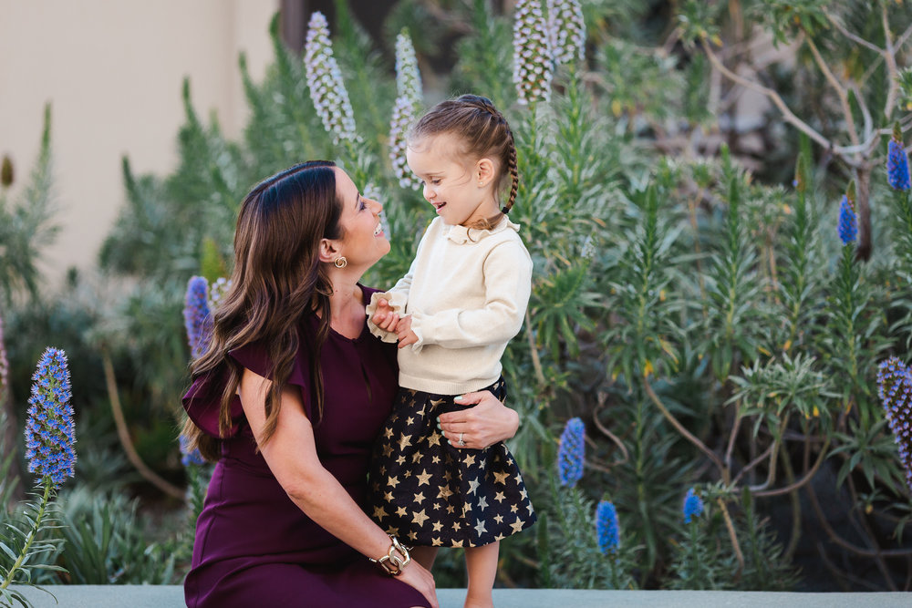 mother and young daughter looking loving at each other surrounded by beautiful purple flowers in La Jolla, California.