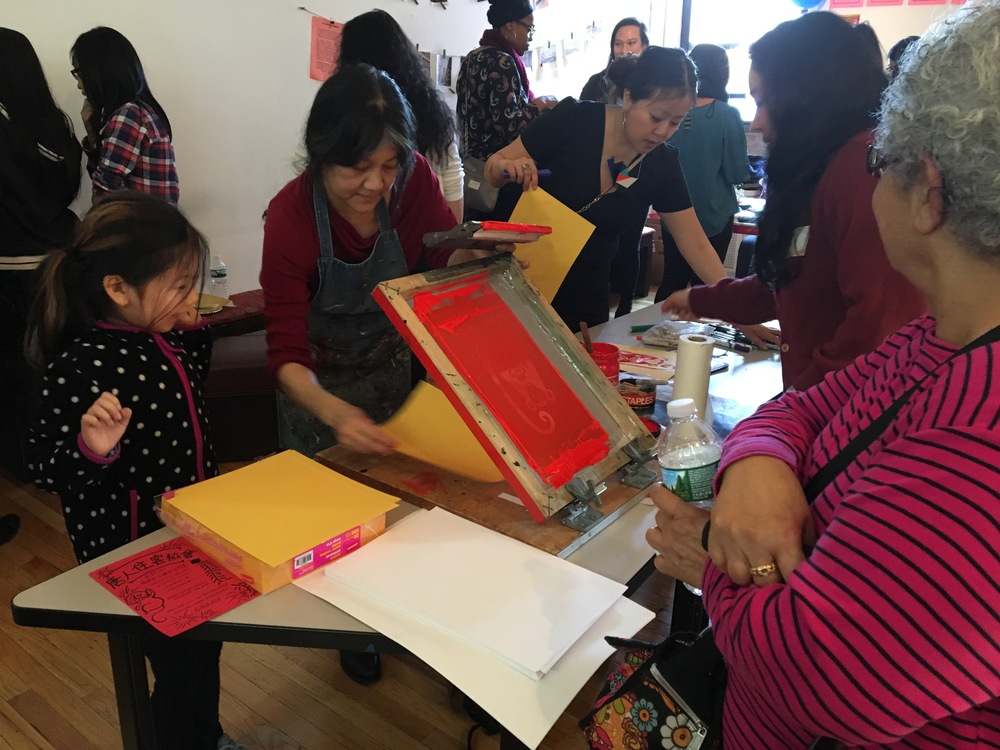 Chinatown Art Brigade teaching silkscreen printing at 2016 CAAAV Chinatown Tenants Union Lunar New Year Celebration