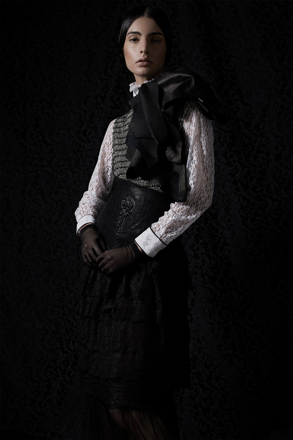 White lace shirt, Numero 21; dress with metallic bodice and black lace skirt, Mori Castello; black underskirt in woven tulle, Mori Castello; black leather necklace with fringe and leather belt with key detail, Zora Romanska