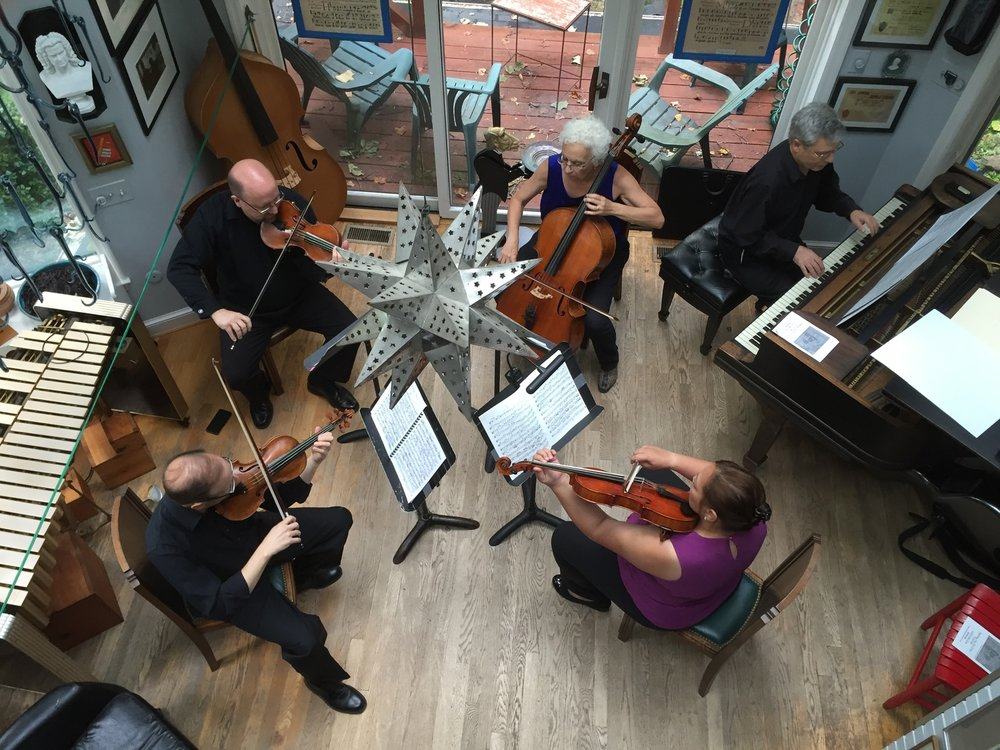 The Trio plus two (Michael Vaughn, violin, Jodi Beder, cello, Carl Banner, piano, joined by Nana Vaughn, viola, and Jeffrey Howard, violin). Photo by Anya Vaughn, at Richard White's on Milo Drive.