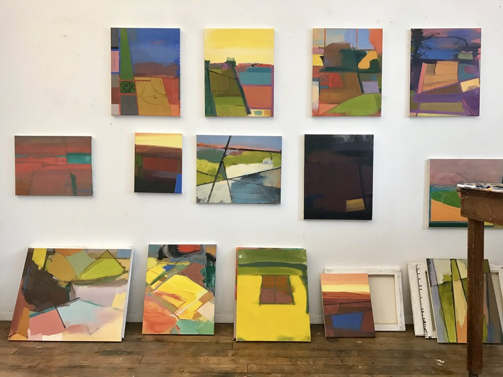Paintings by Elizabeth Hazan hang and lean on the walls in her Brooklyn-based studio. Hazen uses old city maps as influence for her paintings.