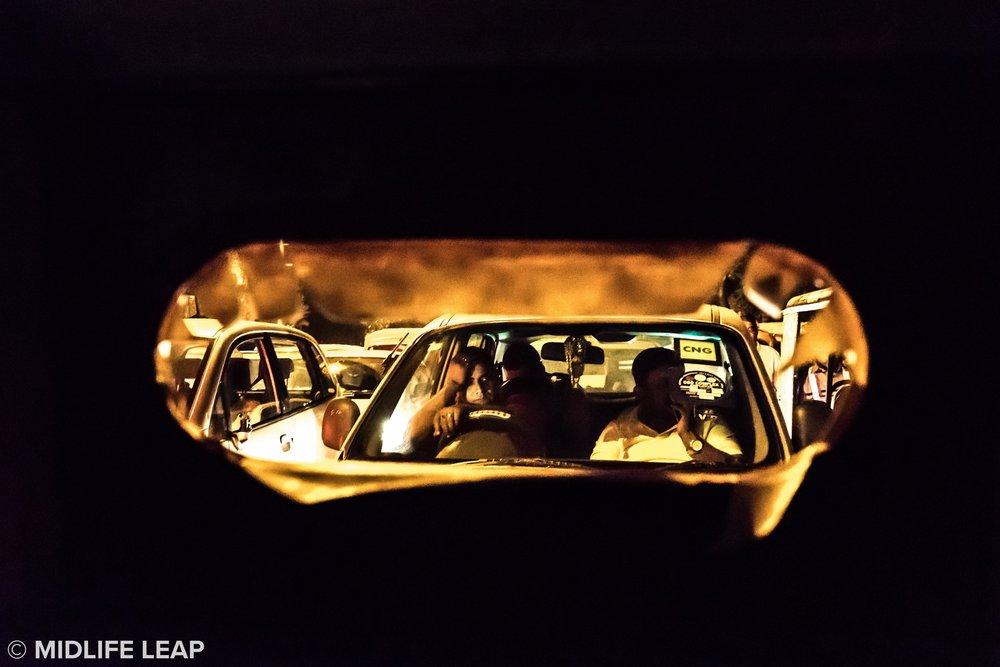 Traffic jam through a broken screen of a rickshaw